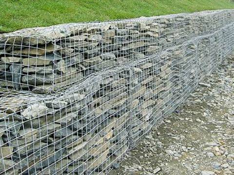 Retaining gabion wall against a slope which is covered by green plants
